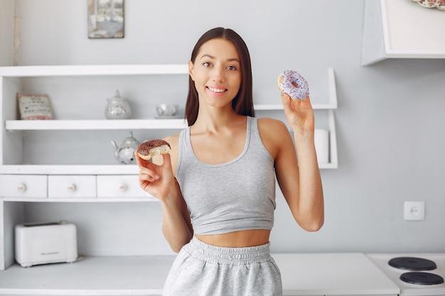 Красивая женщина, стоя на кухне с пончик Бесплатные Фотографии