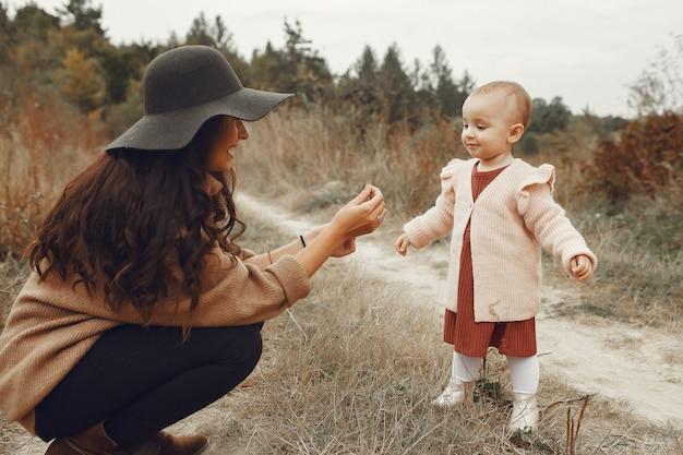 秋のフィールドで遊ぶ幼い娘を持つ母 無料写真