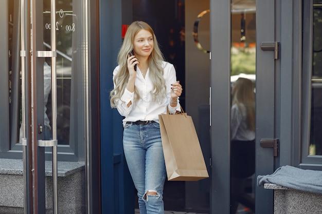 街で買い物袋を持つエレガントな女の子 無料写真