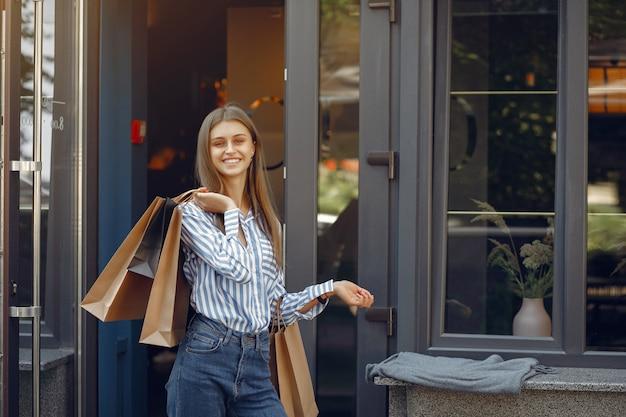 ショッピングバッグと通りのエレガントでスタイリッシュな女の子 無料写真