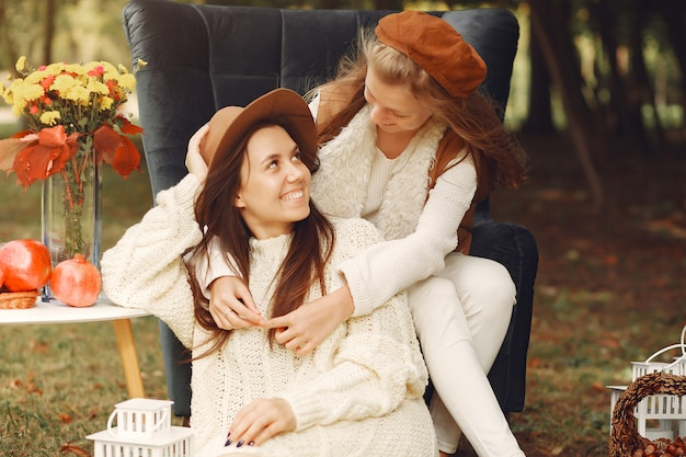 Элегантные и стильные девушки сидят на стуле в парке Бесплатные Фотографии