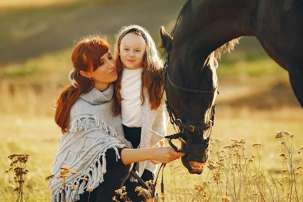 馬と遊ぶ分野で母と娘 無料写真