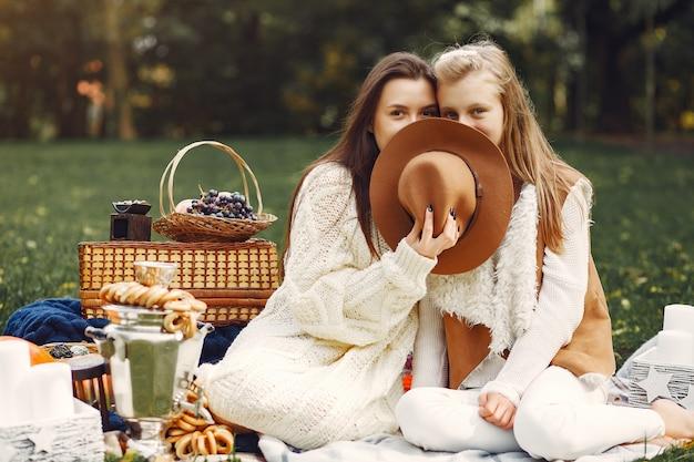 Элегантные и стильные девушки сидят в осеннем парке Бесплатные Фотографии