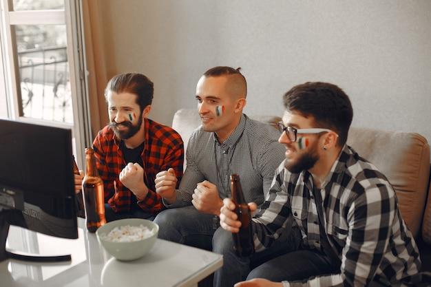 ファンのグループはテレビでサッカーを見ています 無料写真