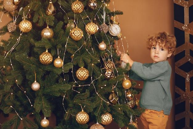 灰色のセーターでクリスマスツリーの近くの小さな男の子 無料写真