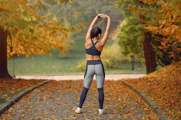 秋の公園で黒のトップトレーニングでスポーツ少女 無料写真