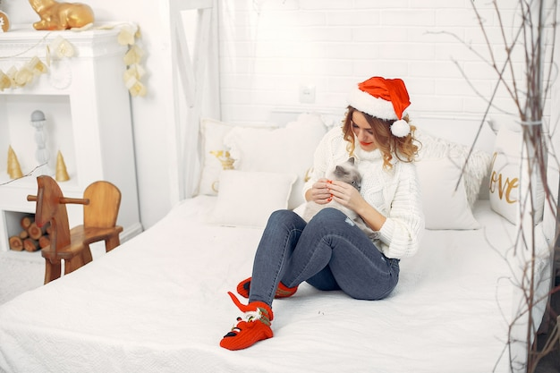 Красивая девушка сидит на кровати с милой кошечкой Бесплатные Фотографии