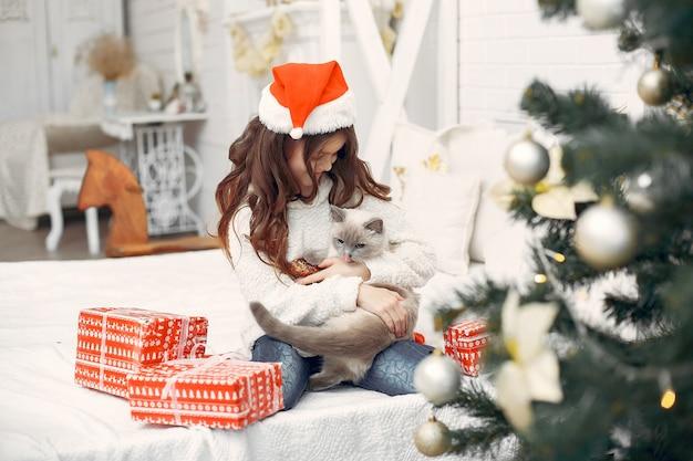 かわいい子猫とベッドの上に座っている少女 無料写真