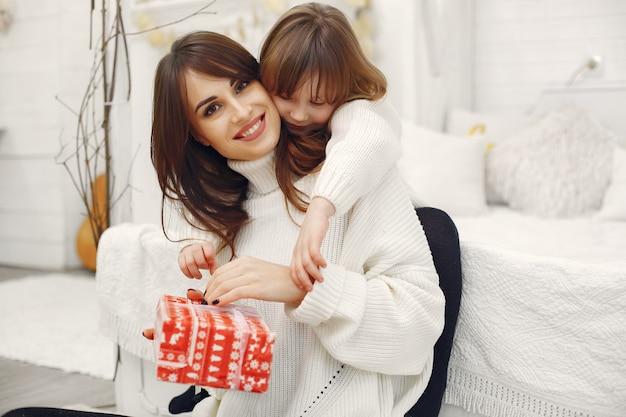 Мать с милой дочерью дома с рождественскими подарками Бесплатные Фотографии