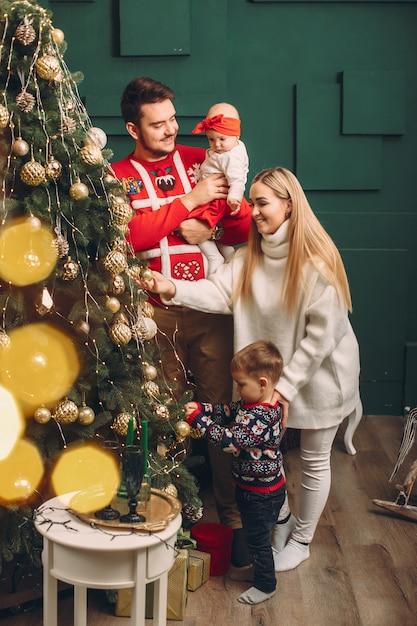 クリスマスツリーの近くに自宅で家族 無料写真