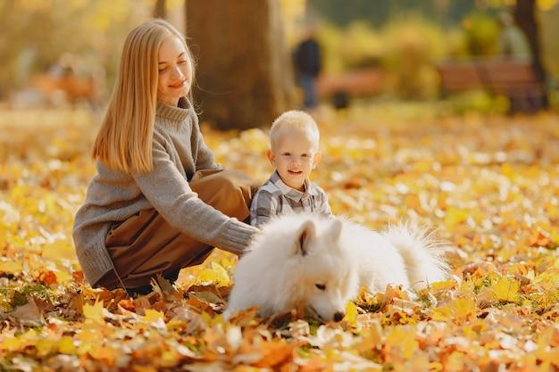 Мать с маленьким сыном сидит в осеннем поле Бесплатные Фотографии