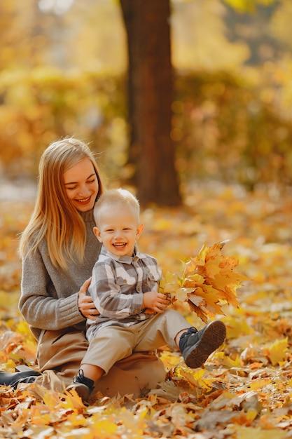 Мать с маленьким сыном, играя в осеннем поле Бесплатные Фотографии