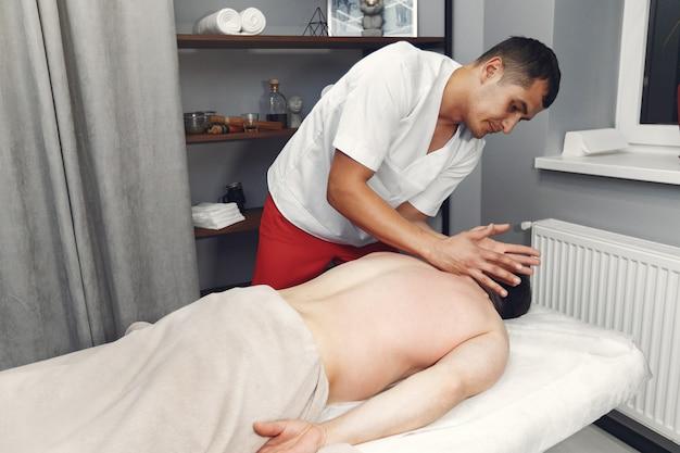 医者は病院で男をマッサージします 無料写真