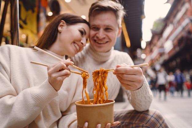 上海の食品市場の外で箸で麺を食べる新婚カップル 無料写真
