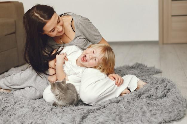母と幼い息子の家で猫と楽しい 無料写真