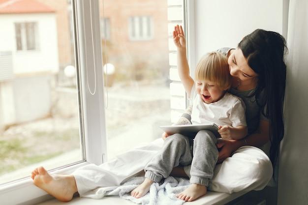 Мать и маленький сын, сидя на подоконнике Бесплатные Фотографии