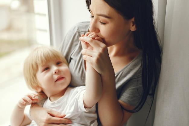母と幼い息子が窓辺に座って 無料写真