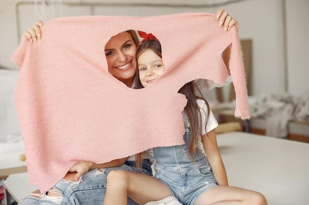 小さな娘を持つ母は、裁縫用の生地を測定します。 無料写真