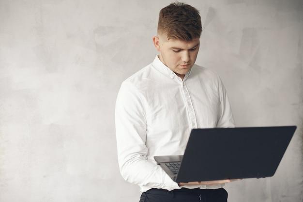 オフィスで働くスタイリッシュなビジネスマンとラップトップを使用する 無料写真