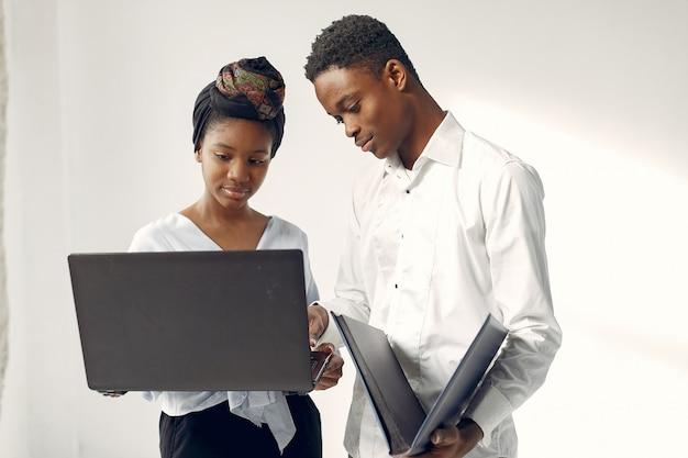 ラップトップで白い壁に立っている黒人 無料写真