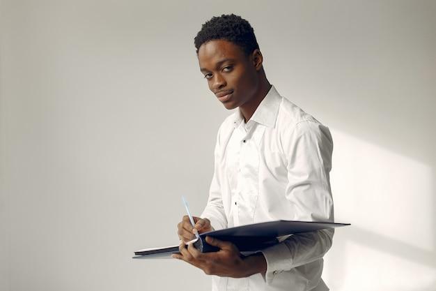 白い壁に立っているハンサムな黒人男性 無料写真
