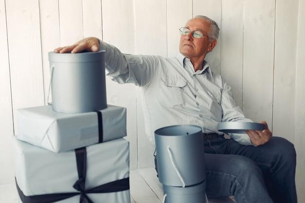 クリスマスプレゼントを自宅で座っているエレガントな老人 無料写真