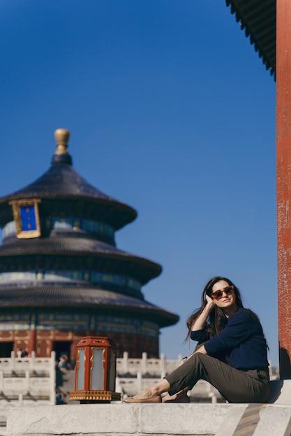 Брюнетка сидит на ступеньках у храма хевен в китае Бесплатные Фотографии