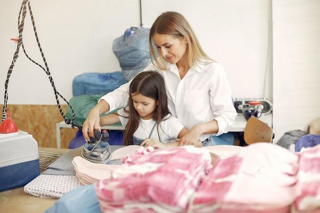 工場で生地をアイロン小さな娘を持つ母 無料写真