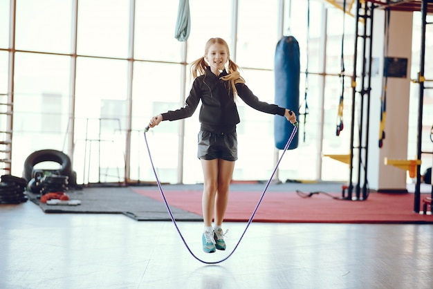 Красивая маленькая девочка занимается в тренажерном зале Бесплатные Фотографии