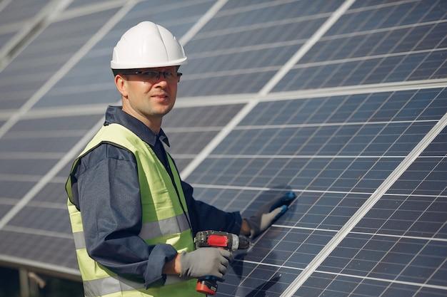 ソーラーパネルの近くの白いヘルメットを持つ男 無料写真