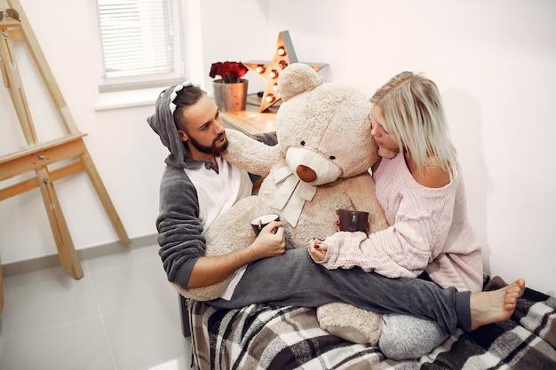 Пара сидит на кровати в комнате, пить кофе Бесплатные Фотографии