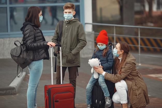 Европейские мамы в респираторах с детьми стоят возле здания. Бесплатные Фотографии