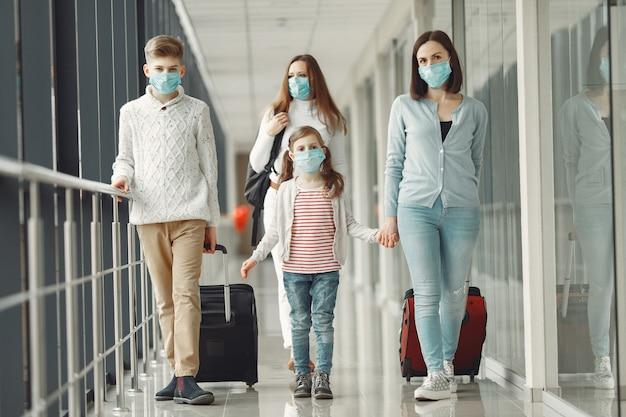 空港の人々は、ウイルスから身を守るためにマスクを着用しています 無料写真