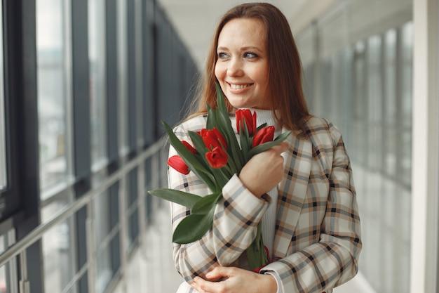 赤いチューリップとかなりヨーロッパの女性は明るいモダンなホール 無料写真