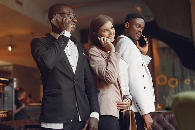 携帯電話でカフェに立っている国際人 無料写真