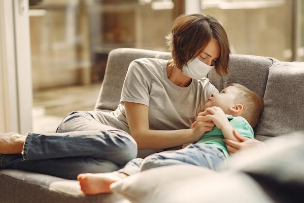 検疫で自宅で座っている小さな息子を持つ母 無料写真