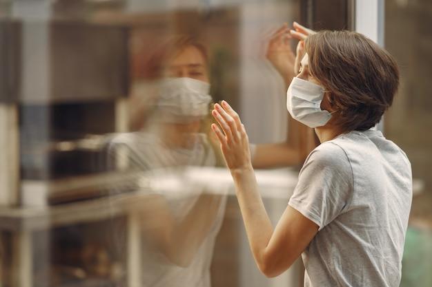 マスクの女性が窓のそばに立つ 無料写真