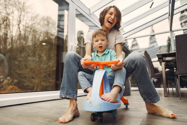 母と息子はおもちゃの車でアパートを回る 無料写真