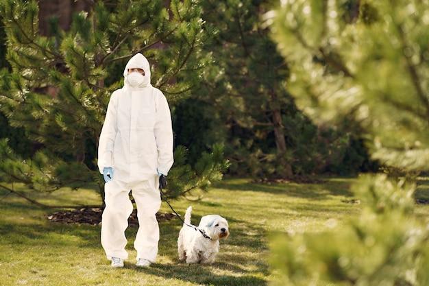 犬と一緒に歩いて防護服の女性 無料写真
