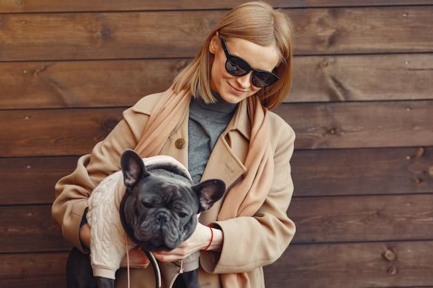 黒いブルドッグと茶色のコートを着たエレガントな女性 無料写真