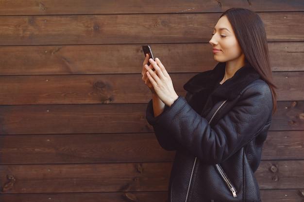 茶色の壁に黒いジャケットスタンディングでエレガントな女性 無料写真
