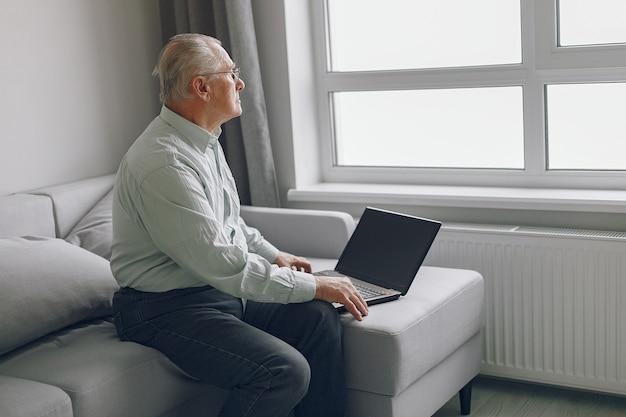 Элегантный старик сидит дома и использует ноутбук Бесплатные Фотографии