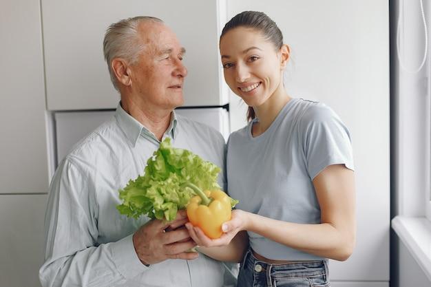 若い孫娘とキッチンで老人 無料写真