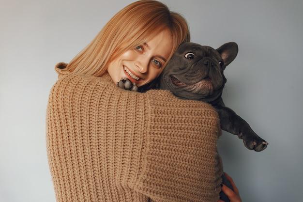 Женщина в коричневом свитере с черным бульдогом Бесплатные Фотографии