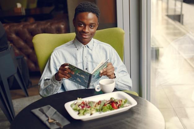 Черный человек сидит в кафе и ест овощной салат Бесплатные Фотографии