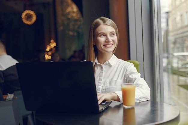 Элегантная женщина в белой блузке работает в кафе Бесплатные Фотографии