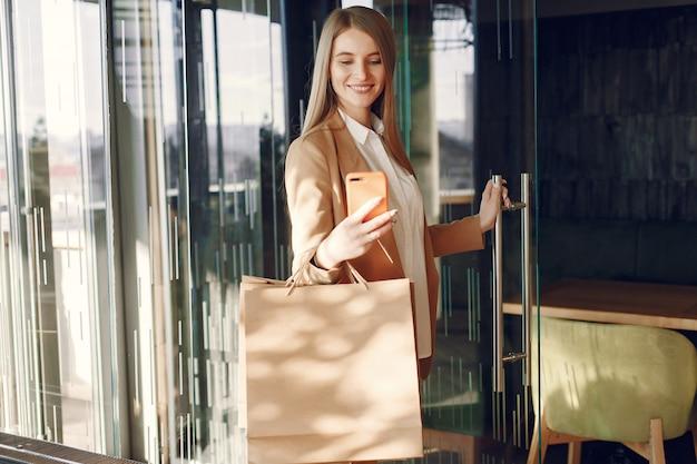 買い物袋付きのカフェに立っているスタイリッシュな女の子 無料写真