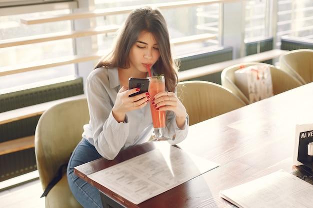 Элегантная женщина в синей блузе, проводя время в кафе Бесплатные Фотографии