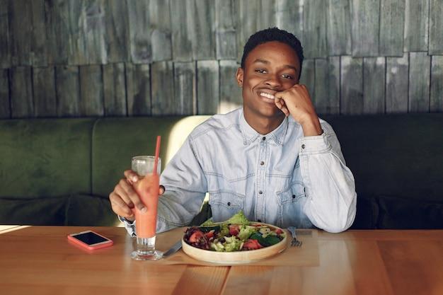 カフェに座っていると野菜のサラダを食べる黒人男性 無料写真
