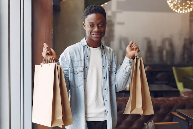ショッピングバッグ付きのカフェに立っている黒人男性 無料写真